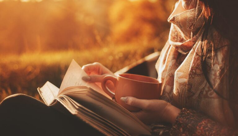 A woman reading during fall