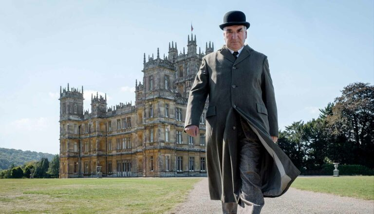 Mr Carson walking in front of Downton Abbey